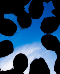 Silhouette of a group of eight people against the sky