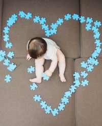 Baby boy sitting in the middle puzzle pieces folded as shape of heart on sofa at home